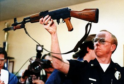 """1989 file photograph: Stockton Police Capt. J.T. Marnoch holds up a Chinese-made AK-47 assault rifle that gunman Patrick Purdy used to kill five schoolchildren and injure 30 others at Cleveland Elementary School in Stockton. (AP Photo/Rich Pedroncelli, File)"""