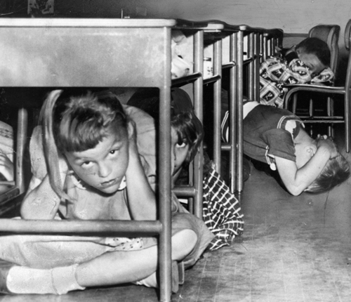 "Cold War children performing a ""Duck and Cover"" drill."