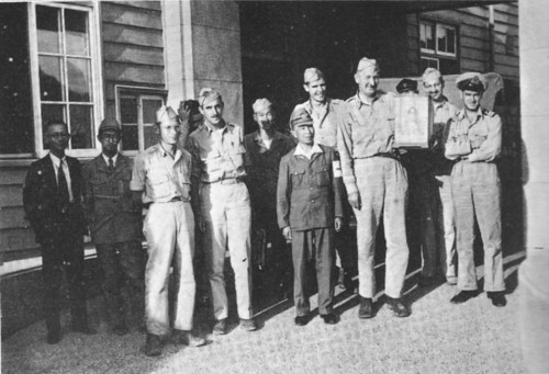 The survey team at Nagasaki. Stafford Warren is the tall man holding a doll given to him as a gift.