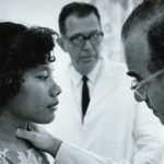 "A medical inspection of a Marshallese woman by an American doctor. ""Project 4,"" the biomedical effects program of Operation Castle was initially to be concerned with ""mainly neutron dosimetry with mice"" but after the accident an additional group, Project 4.1, was added to study the long-term exposure effects in human beings — the Marshallese. Image source."