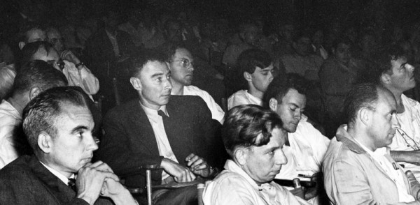 Los Alamos colloquium from 1946, featuring (foreground, from left-to-right), Norris Bradbury, J. Robert Oppenheimer, John Manley, Richard Feynman, and Enrico Fermi. This version is cropped from the scanned copy at the Emilio Segrè Visual Archives. I will note that unlike the more common copies of this photo that have circulated, you can actually get a sense for how many other people were in the room — it looks like a really packed house.