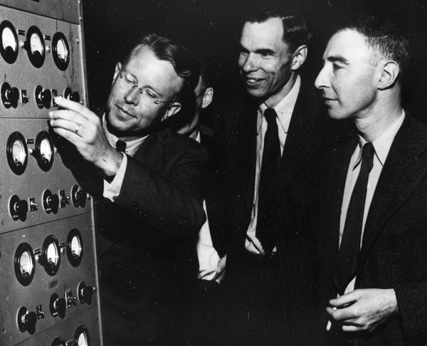 Lawrence, Glenn T. Seaborg, and J. Robert Oppenheimer operate a cyclotron for the cameras in a postwar photograph. Small historical detail (literally): one can find this photograph sometimes flipped on its horizontal axis. Which is the correct orientation? One can take guesses based on rings, handedness, etc., but the copy of the scan that I have has sufficient resolution that you can read the dials, which I think resolves the question. Credit: Emilio Segrè Visual Archives.