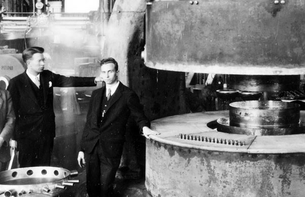 """Lawrence and the Machine. (And M. Stanley Livingston, the one-time grad student who got the machines working.) I like the symbolism of this photo— Lawrence looking at the newest piece of hardware, Livingston with a hand on it, staring the camera down. They are with the 85-ton magnet of the 27"""" cyclotron, circa 1934. Credit: Emilio Segrè Visual Archives."""