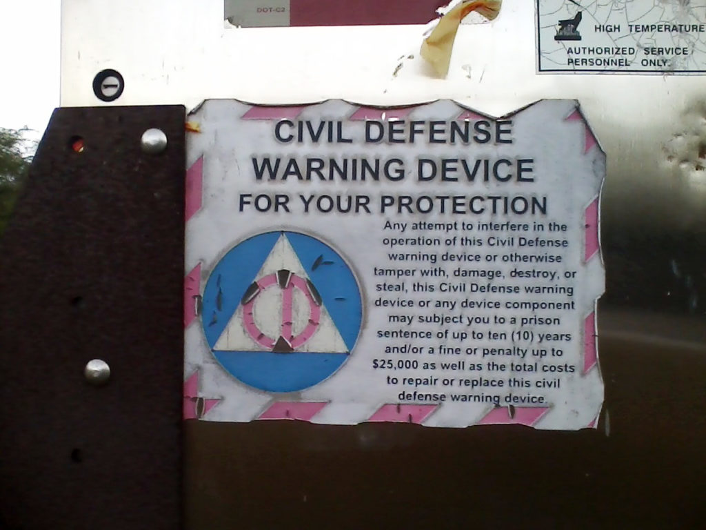 The sign from the base of a tsunami warning siren tower, which is labeled 'Civil Defense Warning Device' and uses an outdated, 1950s Civil Defense logo on it.