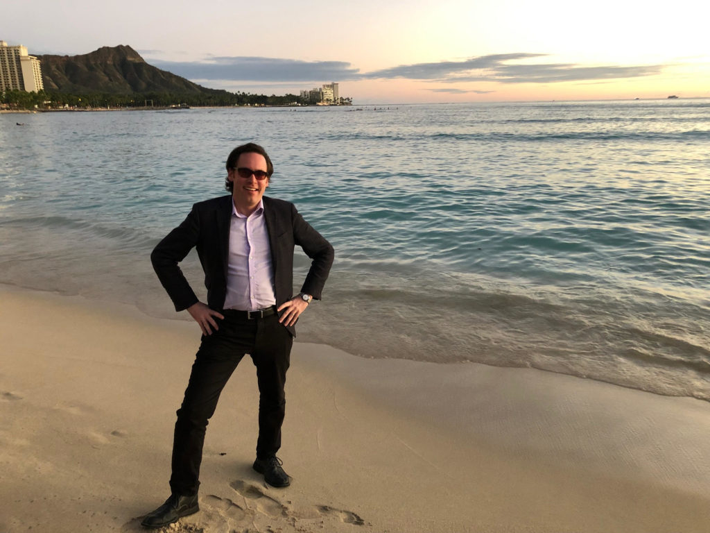 Photo of the author on the beach, wearing inappropriate attire.